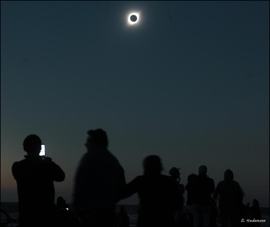 the totally eclipsed sun being observed by hundreds of Chileans and foreigners on the beach